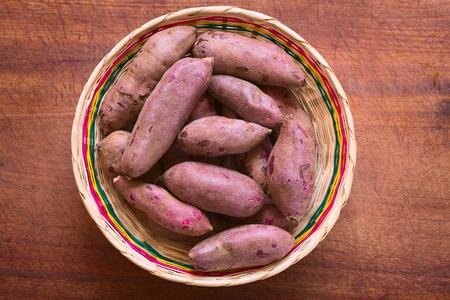 Overhead schot van rauwe paarse zoete aardappel (lat. Ipomoea batatas) in geweven mand op houten plank gefotografeerd met natuurlijk licht