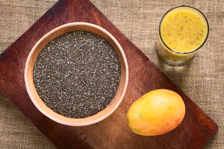 hispanica: Overhead shot of chia seeds (lat. Salvia hispanica) in clay bowl with mango and mango-chia juice photographed with natural light. Chia seeds are considered a superfood containing proteins, omega fats, minerals and antioxidants Stock Photo