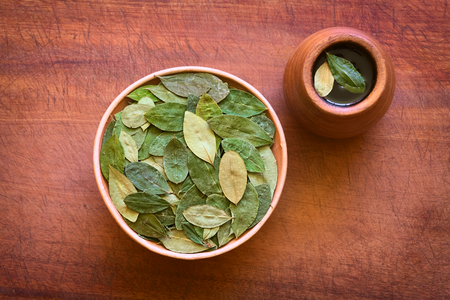 mate infusion: Overhead shot of dried coca leaves in bowl with fresh coca tea (mate de coca) on wood, photographed with natural light Stock Photo
