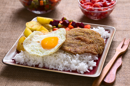Traditional Bolivian dish called Silpancho, which is the name of the breaded flat, round piece of beef meat, served with fried egg, rice, fried potatoes and vegetables (carrot, bean, beetroot), photographed with natural light (Selective Focus, Focus one t