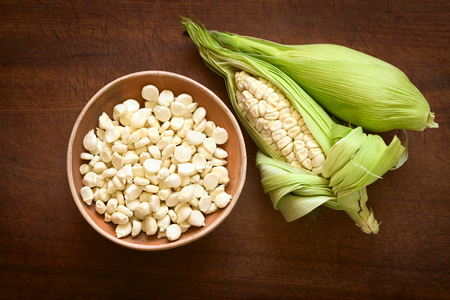 typically english: Overhead shot of kernels in bowl and cobs of white corn called Choclo (Spanish), in English Peruvian or Cuzco corn, typically found in Peru and Bolivia, photographed on wooden board with natural light