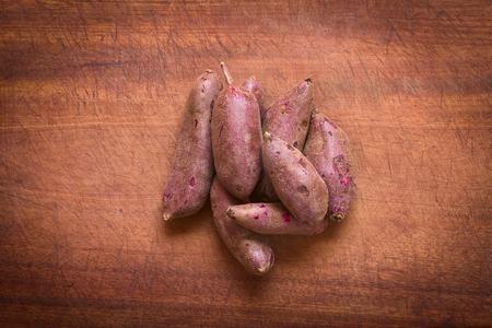 Overhead-Schuss von rohem lila Süßkartoffeln (lat. Ipomoea Batatas) auf Holzbrett mit natürlichem Licht fotografiert Standard-Bild - 37176169