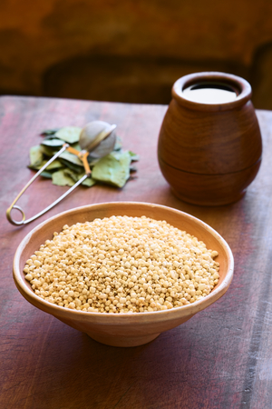 popped: Popped white quinoa (lat. Chenopodium quinoa) cereal in bowl with coca leaves and tea in the back photographed with natural light (Selective Focus, Focus one third into the quinoa cereal)