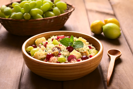 couscous: Vegetarian couscous salad with grapes, pomegranate, walnuts, cheese, lime and mint in wooden bowl photographed with natural light (Selective Focus, Focus on the mint leaf on the dish)