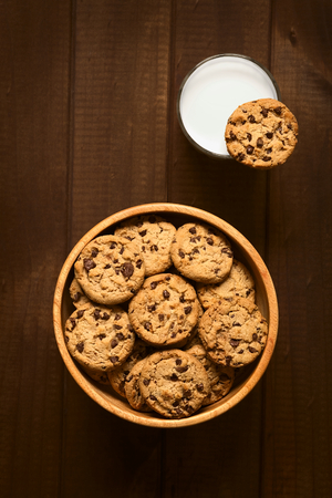 Overhead shot of chocolate chip cookies in wooden bowl and a cookie on the rim of a glass of cold milk, photographed on wood with natural light photo