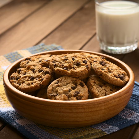 Chocolate chip cookies in wooden bowl with a glass of cold milk in the back, photographed on cloth on wood with natural light (Selective Focus, Focus in the middle of the cookies)