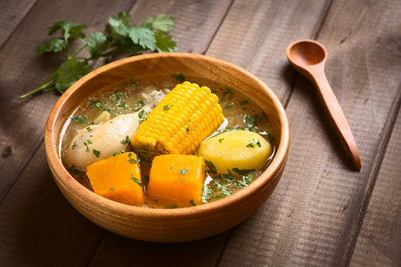 Traditional Chilean Cazuela de Pollo (or Cazuela de Ave) soup made of chicken, sweetcorn, pumpkin and potato, seasoned with fresh coriander served in wooden bowl, photographed on wood with natural light (Selective Focus, Focus one third into the soup)