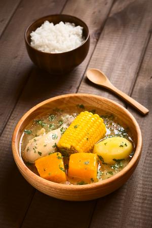 choclo: Cazuela tradicional chilena de Pollo (o Cazuela de Ave) sopa de pollo, ma�z, calabaza y la patata, sazonado con cilantro fresco servido en un taz�n de madera con arroz en la parte de atr�s (que por lo general se come con la sopa), fotografiado en la madera con natur