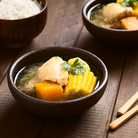 cazuela: Traditional Chilean Cazuela de Pollo (or Cazuela de Ave) soup made of chicken, sweetcorn, pumpkin and potato, garnished with coriander leaf served in bowl with rice in the back (which is usually eaten with the soup), photographed on wood with natural ligh