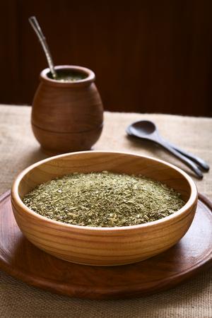 yerba mate: Yerba mate sudamericana (yerba mate) hojas secas en un taz�n de madera con una taza gemela de madera y colador (bombilla) en la parte posterior, fotografiada con luz natural. El mate es la infusi�n nacional de Argentina. (Enfoque selectivo, enfoque un tercio en el t� seco)