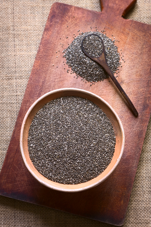 hispanica: Overhead shot of chia seeds (lat. Salvia hispanica) in clay bowl photographed on wooden board with natural light. Chia seeds are considered a superfood containing proteins, omega fats, minerals and antioxidants (Selective Focus, Focus on the seeds in the