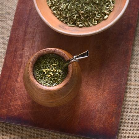 yerba mate: Sudamericano té de yerba mate en una taza gemela de madera con filtro llamado bombilla, fotografiada con luz natural. El mate es la infusión nacional de Argentina. (Enfoque selectivo, centrarse en el té en la taza) Foto de archivo