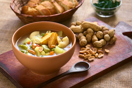 Bowl of traditional Bolivian Sopa de Mani (peanut soup) made of meat, pasta, vegetables (pea, carrot, potato, broad bean, pepper, corn) and ground peanut, photographed on wooden board with natural light (Selective Focus, Focus in the middle of the soup) Stockfoto