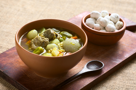 haba: Bolivian traditional soup called Chairo de Tunta (tunta is a freeze-dried potato typical in the Andean regions) made of tunta, beef, broad beans, peas and carrots, uncooked tunta in the back, photographed with natural light (Selective Focus, Focus one thi Stock Photo