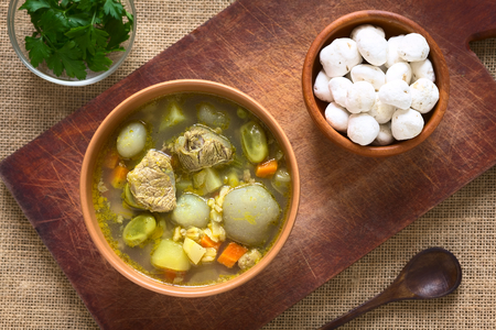 haba: Overhead shot of traditional Bolivian soup called Chairo de Tunta (tunta is a freeze-dried potato typical in the Andean regions) made of tunta, beef, broad beans, peas and carrots, uncooked tunta on the right, photographed with natural light