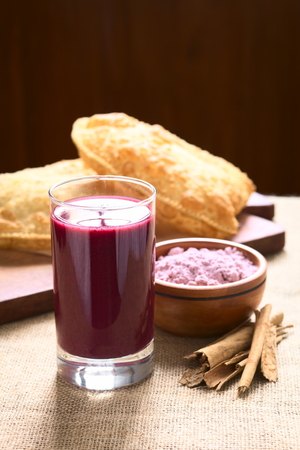 api: Traditional Bolivian Api, a purple corn beverage, with pastel (deep-fried pastry filled with cheese) in the back, photographed with natural light (Selective Focus, Focus on the front of the drink)