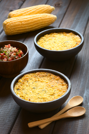 de focus: Bowls of traditional Chilean corn pie called Pastel de Choclo served with Pebre sauce in the back, photographed on dark wood  with natural light. Below the corn-basil mix is ground meat, olive, boiled egg, raisins and pieces of chicken. (Selective Focus,  Stock Photo