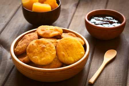 Traditional Chilean Sopaipilla fried pastry made with mashed pumpkin in the dough, served with Chancaca sweet sauce, photographed on wood with natural light (Selective Focus, Focus on the first two sopaipillas) Stockfoto