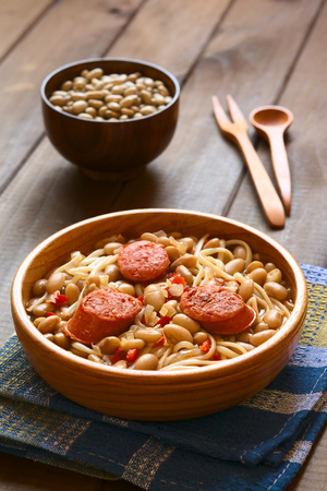 Traditional Chilean dish called Porotos con Riendas (English: beans with reins), made of cooked beans, linguine (flat spaghetti) and served with fried sausage, photographed on dark wood with natural light (Selective Focus, Focus on the two sausage pieces  photo