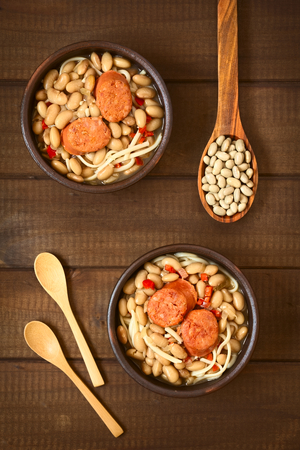 Overhead shot of traditional Chilean dish called Porotos con Riendas (English: beans with reins), made of cooked beans, linguine (flat spaghetti) and served with fried sausage, photographed on wood with natural light photo