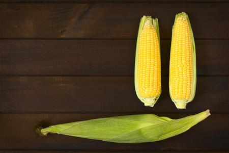 elote: Tiro de arriba de mazorcas de maíz dulce con la cáscara y dos sin cáscara fotografiado en madera oscura con luz natural