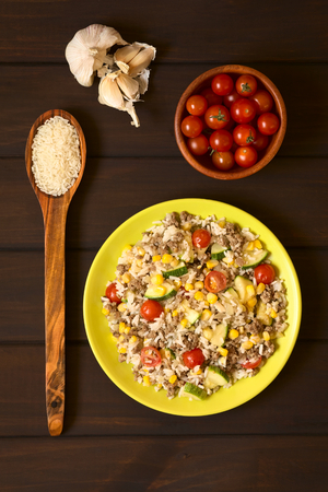 Overhead shot of rice dish with mincemeat and vegetables (sweet corn, cherry tomato, zucchini, onion) served on plate with ingredients around, photographed on dark wood with natural light photo