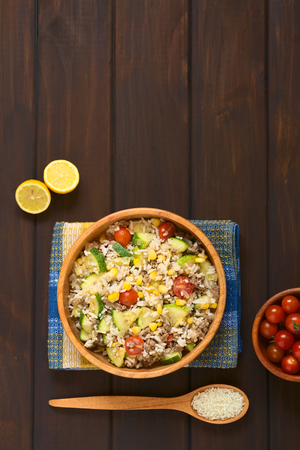 mincemeat: Overhead shot of rice dish with mincemeat and vegetables (sweet corn, cherry tomato, zucchini, onion) in wooden bowl with ingredients on the side, photographed on dish towel on dark wood with natural light