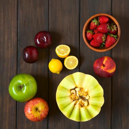 light breakfast: Overhead shot of a variety of fresh fruits (honeydew melon, nectarine, apple, strawberry, plum, lemon), photographed on dark wood with natural light Stock Photo
