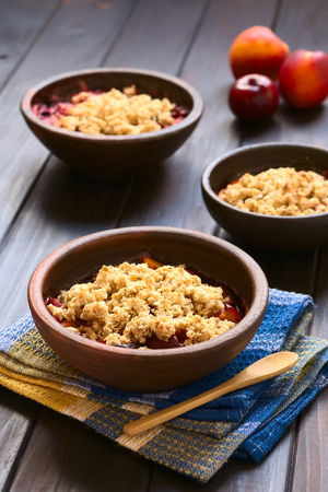 crumbly: Three rustic bowls filled with baked plum and nectarine crumble or crisp, photographed on dark wood with natural light (Selective Focus, Focus one third into the first dessert) Stock Photo