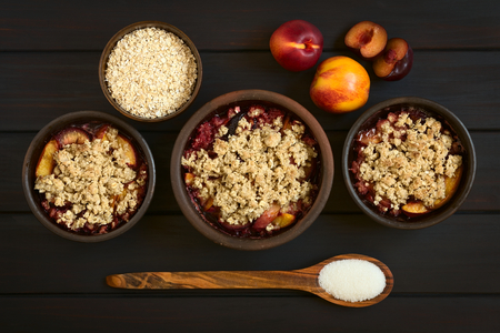 plum pudding: Overhead shot of three rustic bowls filled with baked plum and nectarine crumble or crisp, photographed on dark wood with natural light