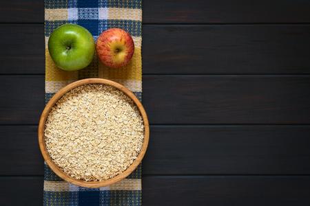 avena en hojuelas: Tiro de arriba de copos de avena primas en cuenco de madera con las manzanas en tela, fotografiado en madera oscura con luz natural