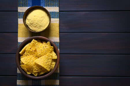 Overhead shot of tortilla chips and cornmeal in bowls on kitchen towel, photographed on dark wood with natural light photo