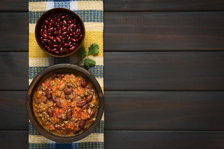 Overhead shot of chili con carne and dried kidney beans in bowls on kitchen towel Stock Photo