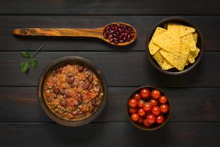 chilli: Overhead shot of chili con carne and tortilla chips with ingredients dried kidney beans and cherry tomatoes Stock Photo