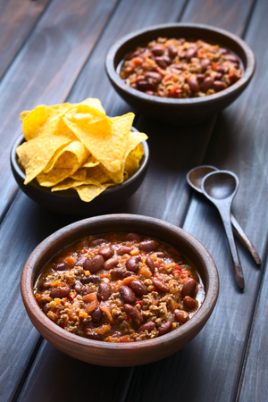 Two rustic bowls of chili con carne with tortilla chips in the back