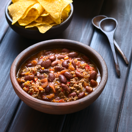 Rustic bowl of chili con carne with tortilla chips in the back