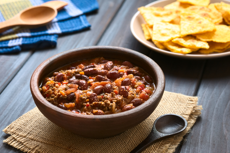 Rustic bowl of chili con carne with homemade tortilla chips in the back, photographed with natural light Stock fotó