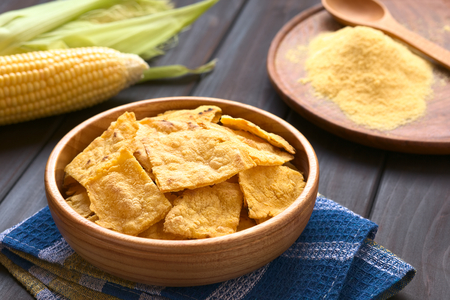 corn chip: Wooden bowl of homemade baked corn chips with cobs of corn and cornmeal in the back, photographed with natural light Stock Photo