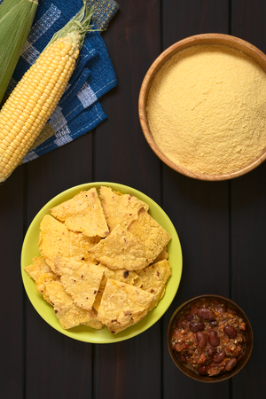 corn chip: Overhead shot of homemade baked corn chips on plate with cornmeal, corn cobs and a small bowl of chili con carne