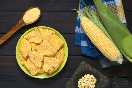 Overhead shot of homemade baked corn chips on plate with cornmeal, corn cobs and corn kernels in mortar