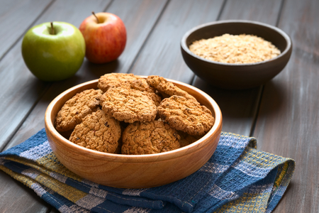 Oatmeal and apple cookies in wooden bowl with apples and oatmeal in the back, photographed with natural light (Selective Focus, Focus on the front of the cookie in the middle)