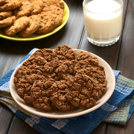oatmeal cookie: Chocolate oatmeal cookies on plate with a glass of milk and oatmeal-apple cookies in the back, photographed with natural light