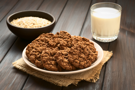 Chocolate oatmeal cookies on plate with a glass of milk and a bowl of oatmeal in the back, photographed with natural light photo