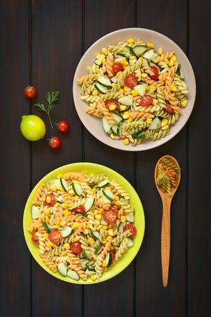 Overhead shot of two plates of vegetarian pasta salad made of tricolor fusilli, sweet corn, cucumber and cherry tomato photo