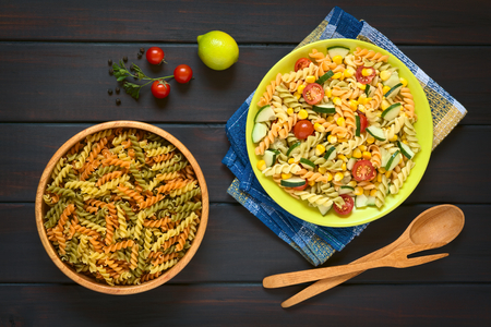 overhead shot: Overhead shot of raw fusilli pasta in wooden bowl and a plate of vegetarian pasta salad made of tricolor fusilli, sweet corn, cucumber and cherry tomato, photographed on dark wood with natural light