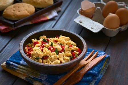 scrambled eggs: Scrambled eggs made with red bell pepper and green onion in rustic bowl with toasted bread and eggs in the back