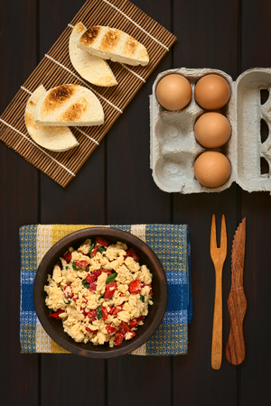 scrambled eggs: Overhead shot of scrambled eggs made with red bell pepper and green onion in rustic bowl with toasted bread and eggs Stock Photo