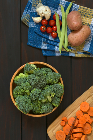 florets: Overhead shot of fresh raw broccoli florets in wooden bowl with carrot slices on wooden board, potato, green bean, cherry tomato and garlic on kitchen towel