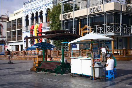 mote: IQUIQUE, CHILE - JANUARY 22, 2015: Unidentified people sitting at Mote con Huesillo (Chilean cold drink) stand on Plaza Prat main square with the building of BBVA bank and the Casino Espanol next to it on January 22, 2015 in Iquique, Chile