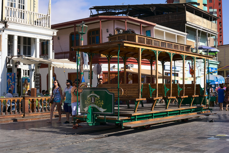 waggon: IQUIQUE, CHILE - JANUARY 22, 2015: Unidentified people around an old open tram waggon with wooden seats on Plaza Prat main square along Baquedano avenue on January 22, 2015 in Iquique, Chile Editorial